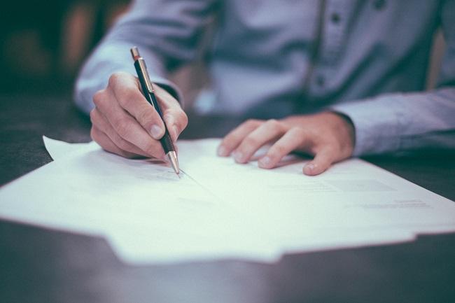 Man completing paperwork at desk